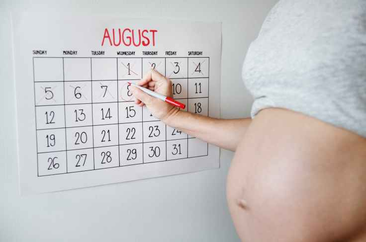 expectant lady holding pen marking calendar